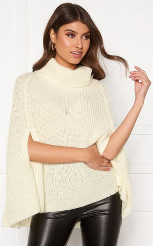 This is an image of the Annabelle knitted poncho. It is a thick, cream coloured knit with arm slits on either side. It has a chunky polo neckline and is ideal styled over leather or wet look jeans.