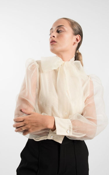 This is an image of the Berta Organza Blouse, it is cream coloured and has an oversized bow on the neckline. It has Mesh Long sleeves with cuffs and a button closure up the centre front.