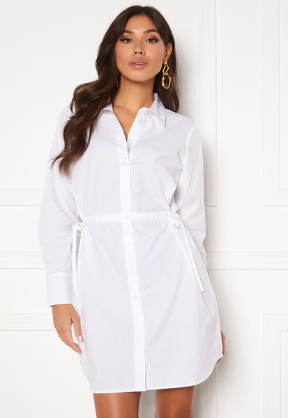 This is an image of The Lorina Cotton Shirt Dress in White. The Lorina is a fine Shirt Dress with Knot Details on the sides and Long Sleeves.  It is made out of a non-stretch, Woven Cotton fabric.  It has button closures the whole way up the front and the fit can be adjusted to your liking with the drawstrings on each side of the waist.  The Sleeve Length can also be adjusted as it has button closures on the cuff.