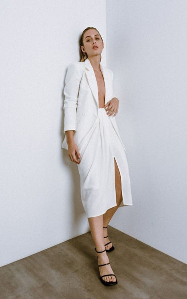 This Knotted Skirt is the Ultimate Wardrobe Staple for Spring/Summer.  It is midi length and fitted with an invisible zip at the back and a large knot detail on the tummy, making it ideal for hiding problem areas.  This Skirt can be worn Casually with Sandals and a Cropped Top, Or dressed up with a Blouse tucked in and some Heels.  Available in White & Black