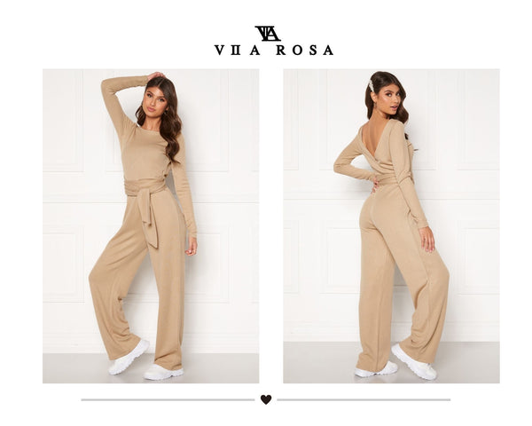 This is an image of the Maya belted knitted jumpsuit. It is beige and has long sleeves and a V at the back. It has wide leg trousers and a thick, long waist belt attached which can be tied in multiple ways