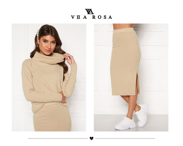 This is an image of the Kimberly knitted beige polo neck jumper styled with the matching knitted midi skirt which has a small split on the right hand side.