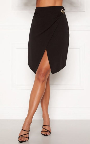 This is an image of the Sophie split front skirt, it falls just below the knee and is black. It has a split in the centre front and two gold emblems on either side of the waist
