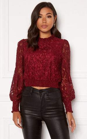 this is an image of the valentina lace blouse which is wine in colour and has lace all over. it has balloon sleeves finished with elasticated cuffs and an elasticated waist band and cropped length