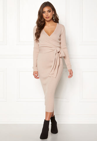 This is an image of the Valerie Knitted Midi Dress. It is a light beige colour with a V neckline and long sleeves. It has a knitted belt attached which can be worn in a bow to the front or wrapped around the back.