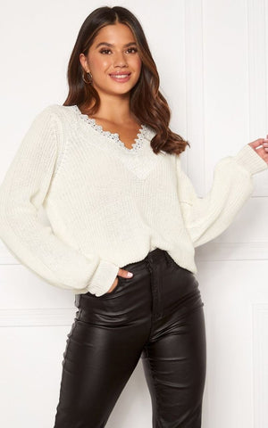this is an image of the wendy cream knittted jumper which has balloon sleeves and a V neckline that is finished with lace. It falls just below the hips and is styled here with black wet look jeans