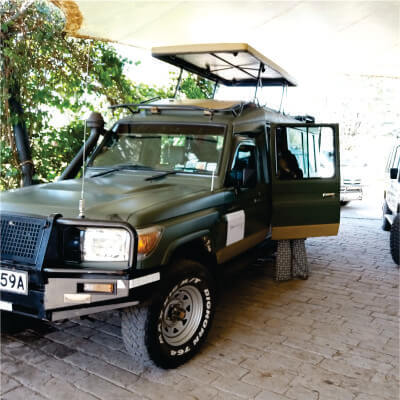 A woman boarding a green 4x4 safari jeep with pop-up top ready to depart from Nairobi to Masai Mara for 3-Day Safari