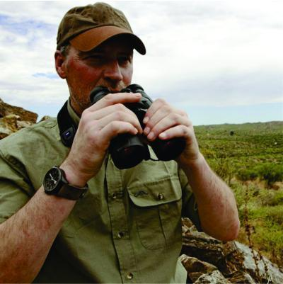 A safari tour operator holding a pair of binocular in Kenya during a 3-Day safari guide to Masai Mara National Reserve