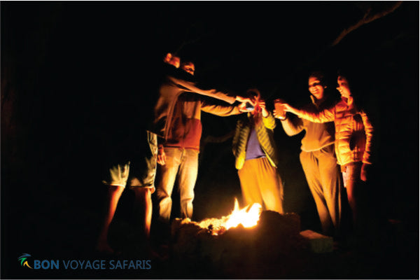 A small group of people standing in front of bonfire in Masai Mara National Reserve during 3 days cheap group camping tours