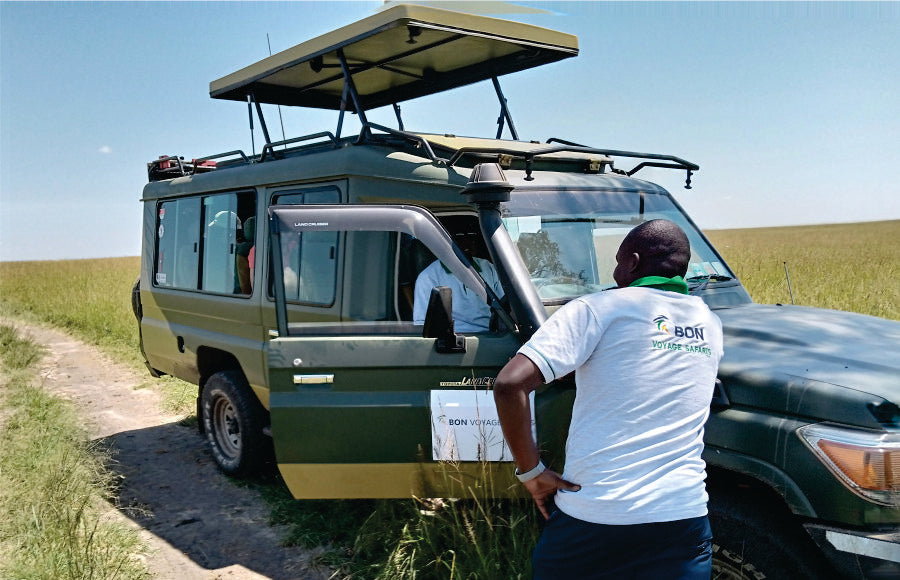 A driver-guide inside a jeep is receiving weather updates from a tour operator putting on a t-shirt with Bon Voyage Safari company logo on it