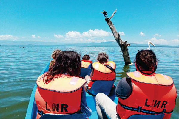 A small group of five people on motorboat enjoying views of birds during a one-hour boat tour at Lake Naivasha in Kenya
