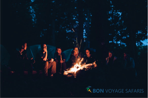A group of people sitting on the front of a firepit at nighttime enjoying each other's company in Masai Mara, Kenya.
