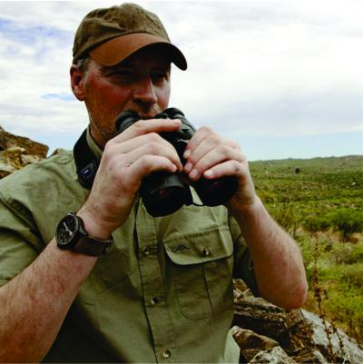 A male travel agent from Bon Voyage Kenya Safaris is holding a pair of binocular during a travel guide in Kenya
