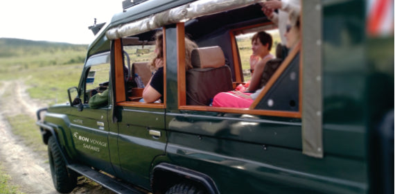 Two people in an open sided 4x4 green safari jeep during 3 days budget tours in the Masai Mara National Reserve