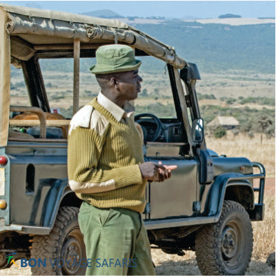 A local private tour guide standing near a green 4x4 jeep in Masai Mara