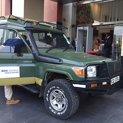 A green safari jeep parked at hotel entrance next to the airport in Nairobi ready transfer of passengers