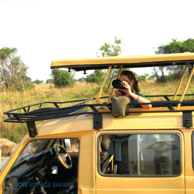 A woman captured taking a photo from a jeep's pop up top during 3 days wildlife safari in Kenya