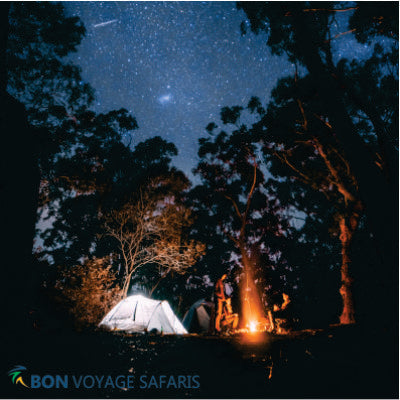 Three people near bonfire and dome tents surrounded by trees in Masai Mara during 3 days cheap group camping tours