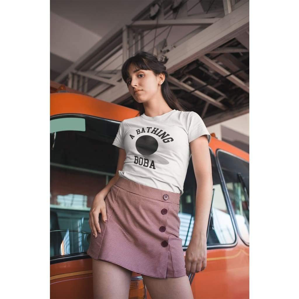 A woman wearing a Bathing Boba shirt posing against a car
