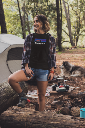 Woman wearing Black Bobagonia shirt standing against the log