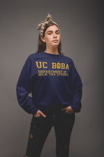 Woman wearing a UC Boba Sweater Against a Grey Background