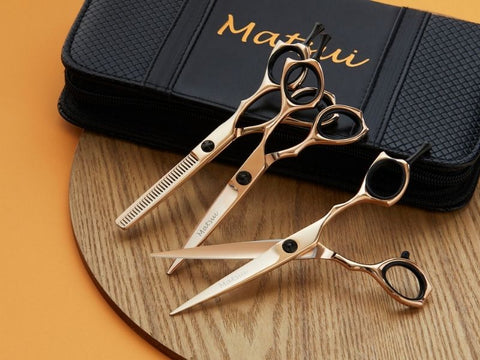 Three pairs of Matsui professional hairdresser scissors in gold and black.
