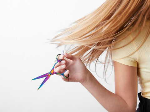 Girl holding scissors away from hair flick