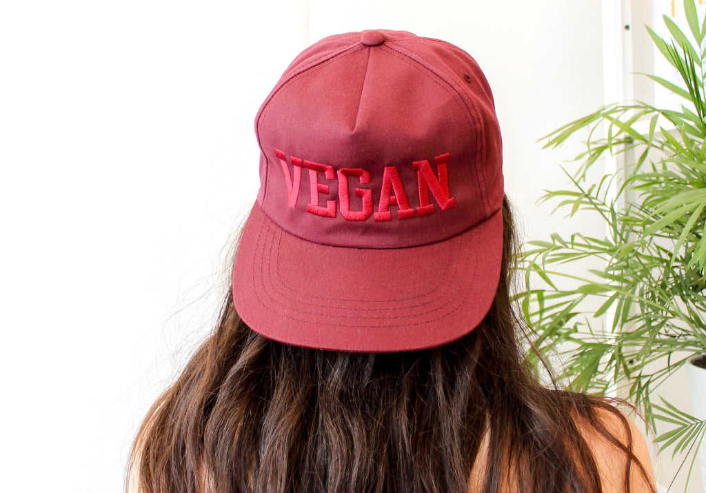 Woman with long hair has her back to the camera and wears a maroon snapback cap that says VEGAN in capital letters