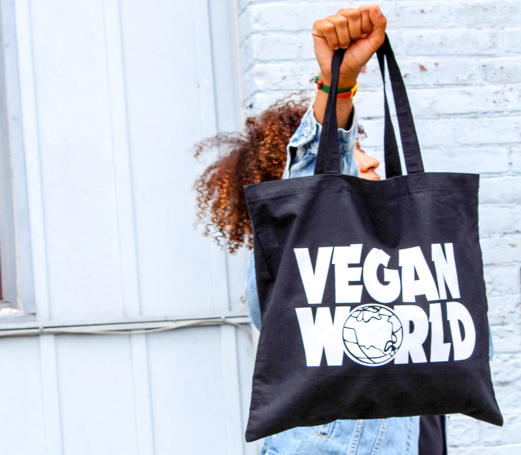 A woman holding up a black tote bag that says Vegan World in homage to the popular Wayne's World font