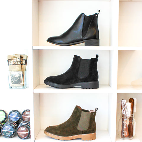 Three pairs of vegan Chelsea boots. Two black pairs made from matte faux leather and one faux suede green pair.