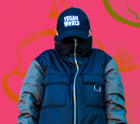 A person wearing a For All Kind Reversible Puffer Jacket which is a black jacket with green sleeves and two pockets on the chest. The jacket is zipped up high so you cannot see their face, on their head they wear a black baseball cap with Vegan World written in white font in homage to the Wayne's World motif