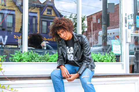 A woman with curled brown hair sat on a bench wearing a vegan leather jacket, a t-shirt that says 'Vegan World' and blue jeans. She looks like a badass.