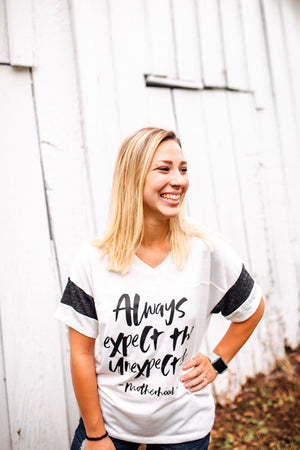 Always Expect The Unexpected Women's Varsity Tee (Eco Ivory/Black + Black)