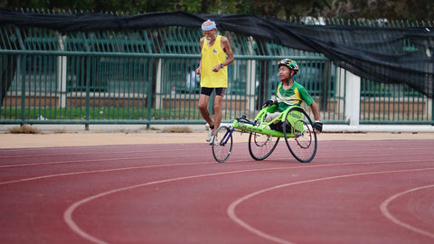 a man in a green sports wheelchair on a track, image by @golfarisa on unsplash