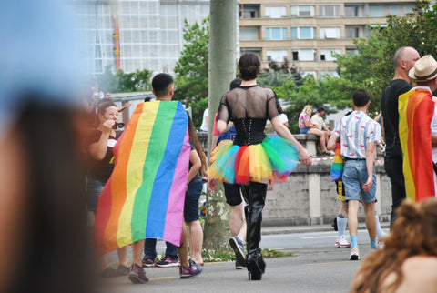 Photo by @dels on unsplash. 2 people at a pride parade, one is wearing a rainbow flag as a cape, the other is wearing a rainbow tutu and a black corset
