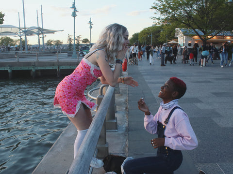 black butch with pink hair proposing to white blonde girl in pink dress. Image by Jakayla Toney on unsplash