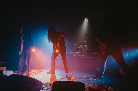metal band performing on stage, they are backlight so their faces and outfits can't be seen