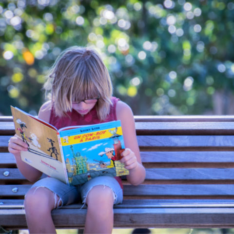 young girl reading book about mindfulness on a park bench