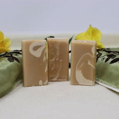 Picture of By the Sea Soap Shoppe Great Goat Soap Mini Soaps standing between green flowered towels with yellow roses in the background. Soap ingredients include goat milk and a