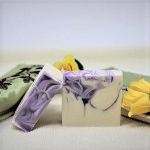 "Two bars of By the Sea Soap Shoppe ""Luscious Lavender"" bars of soap showing the white bars with the purple swirls of colour throughout and the purple swirls on the top of the bar. $7.00 each."