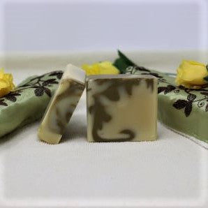 Bu the Sea Soap Shoppe Patchouli soap. Picture shows two bars, one facing, light colour with a forest green swirl of colour. One bar of soap leans against the other showing the design on the top of the bar. Vegan, all-natural, scented with Patchouli essential oil. cost is $7.00