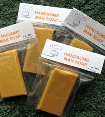 Photo shows three gold coloured By the Sea Soap Shoppe mini soap bars among green flowered towels and yellow roses. This soap contains clove, cinnamon, orange and patchouli essential oils, giving it an appealing, spicy scent. Vegan, natural ingredients, handmade in Prince Edward Island. $3.00 each