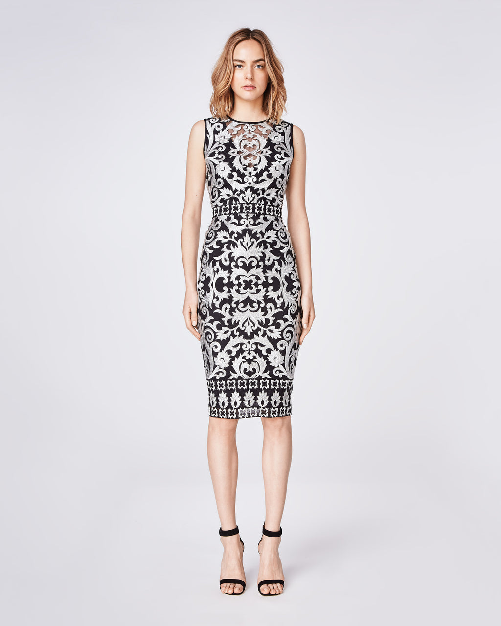 CD10080 - SCROLL EMBROIDERY SLEEVELESS ILLUSION DRESS - dresses - midi - A classic fitted, sleeveless sheath dress is the perfect holiday party staple with gold embroidery detail. It feautures a center back concealed zipper with hook and eye closure. Depending on the event, style it with a leather jacket or wear solo as a statement piece.