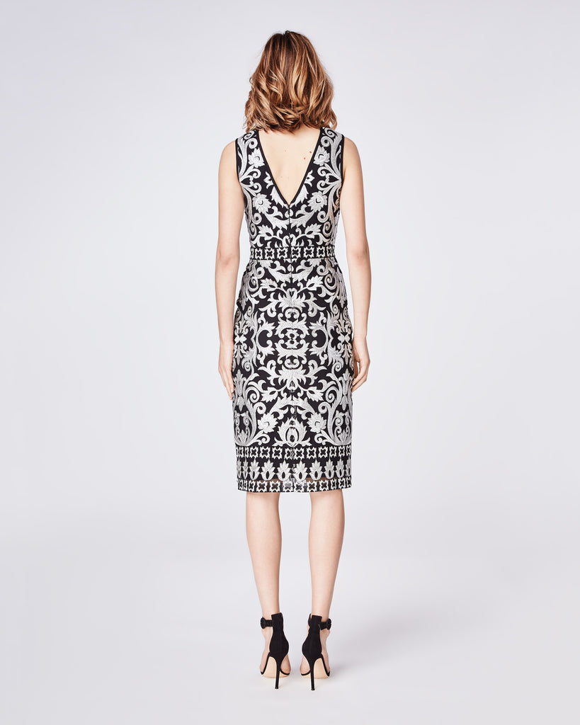CD10080 - SCROLL EMBROIDERY SLEEVELESS ILLUSION DRESS - dresses - midi - A classic fitted, sleeveless sheath dress is the perfect holiday party staple with gold embroidery detail. It feautures a center back concealed zipper with hook and eye closure. Depending on the event, style it with a leather jacket or wear solo as a statement piece. Alternate View