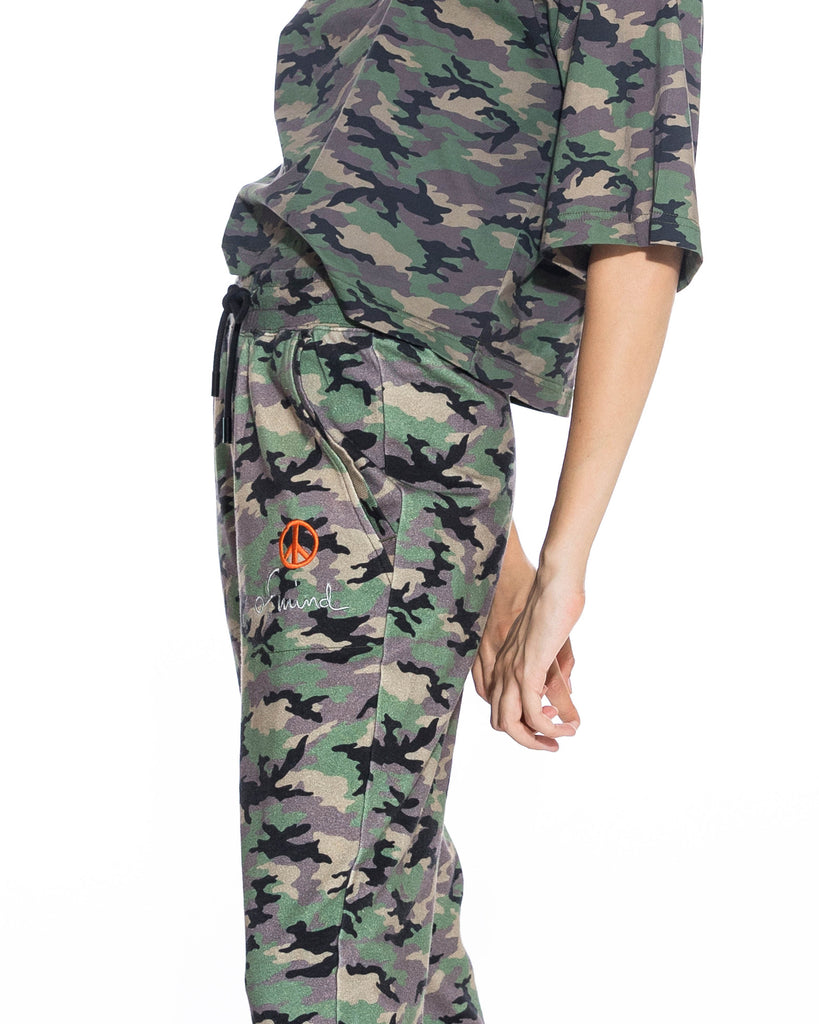"CP18593 - CAMO JOGGER - bottoms - pants - A closet essential. These camo joggers can instantly dress up any plain t-shirt. Featuring a classic jogger fit, drawstring waist and ""peace of mind"" embroidery on the left hand pocket. Add 1 line break Stylist tip: Pair with a classic black tee and chunky gold jewelry. Alternate View"