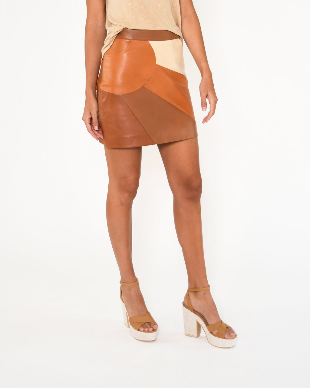 CS18795 - LEATHER PATCHWORK SKIRT - bottoms - skirts - Our patchwork leather mini skirt is designed in buttery leather in rich brown and beiges hues. Pieces are stitched together to create a sunset silhouette along the right hand pocket. Back zipper for closure. Add 1 line break Stylist Tip: Pair with a lightweight sweater and tall brown boots.