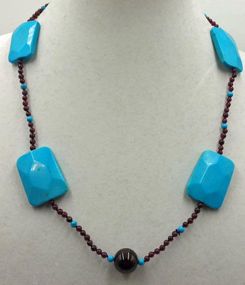 Magnesite, garnet, individually knotted with adjustable sterling necklace on blue silk.