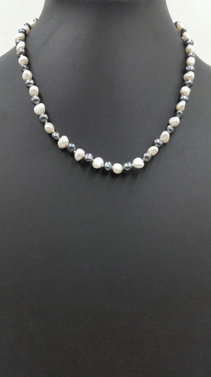 Alternating black & white pearl necklace with sterling silver on baby blue silk.