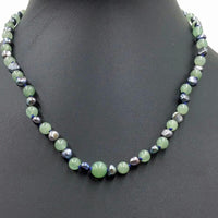 "2-tone jadeite & black pearl, sterling silver, necklace on navy silk. 17.5-19"" Princess length."