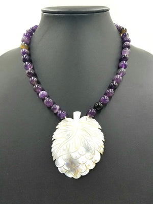 Unusual carved mother of pearl  pendant on amethyst necklace.